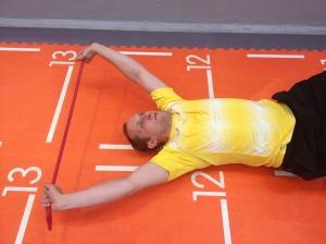 Rulla övre ryggen liggandes på lacrossebollarna med armarna låsta över huvudet (med gummiband)